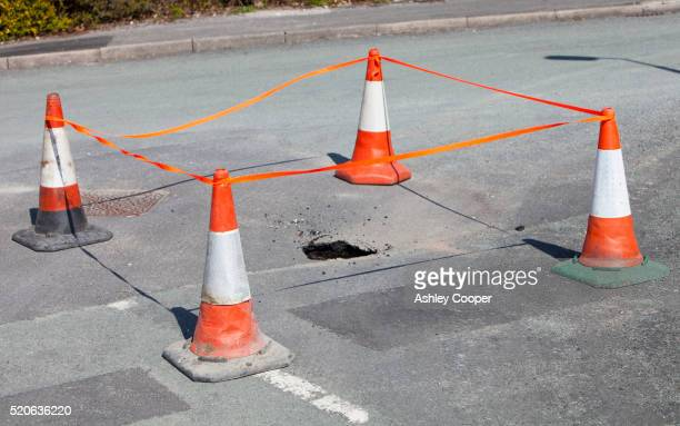 sinkhole opening up in the road in ambleside - sinkholes stock pictures, royalty-free photos & images