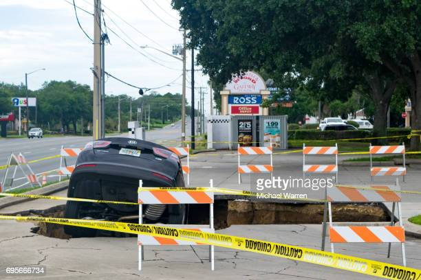 sinkhole swallows a car in florida - cave in collapsing stock photos and pictures