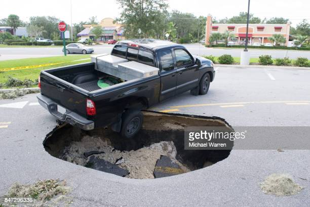 sinkhole swallows a car in florida - pothole stock photos and pictures