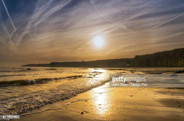 A Sinking Sun Glows In The Sky And Reflects Off The Wet Sand Along The Coast