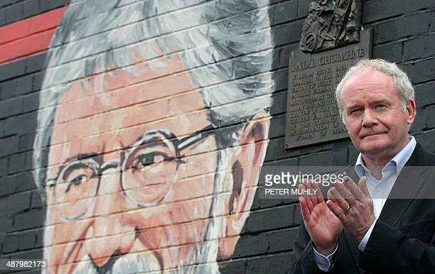 Sinn Fein politician and Northern Ireland's deputy first minister Martin McGuinness applauds the crowd as he speaks against a backdrop of a mural of...
