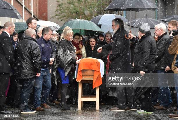 Sinn Fein President Gerry Adams and Sinn Fein Northern Ireland leader lay an Irish flag on the coffin of the late Martin McGuinness watched by his...