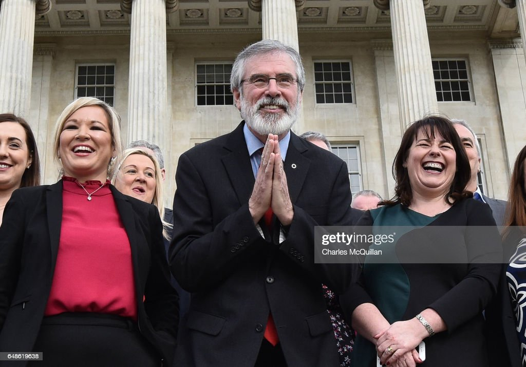 Sinn Fein president Gerry Adams (C) bows to a group of Japenese tourists as he attends a press call alongside northern leader Michelle O'Neill (2nd L) and Michelle Gildernew (R) at Stormont on March 6, 2017 in Belfast, Northern Ireland. Elected MLA's return today after last weeks elections with the two largest parties, Sinn Fein and the Democratic Unionist party commencing talks to form a new power sharing executive government. Sinn Fein northern leader Michelle O'Neill has stated that there can be no agreement if former First Minister Arlene Foster of the DUP is nominated again for the position.