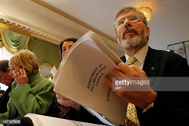 Sinn Fein President Gerry Adams reads over a copy of an agreement on policing and justice before a press conference attended by Northern Ireland's...