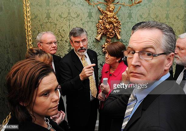 Sinn Fein President Gerry Adams talks to his party members following a press conference attended by Northern Ireland's First Minister Peter Robinson...