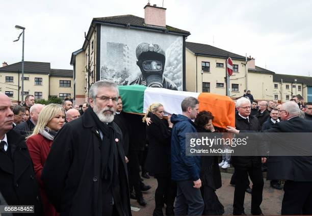 Sinn Fein President Gerry Adams walks alongside Martin McGuinness' coffin carried by his wife Bernadette McGuinness as the funeral cortege passes...