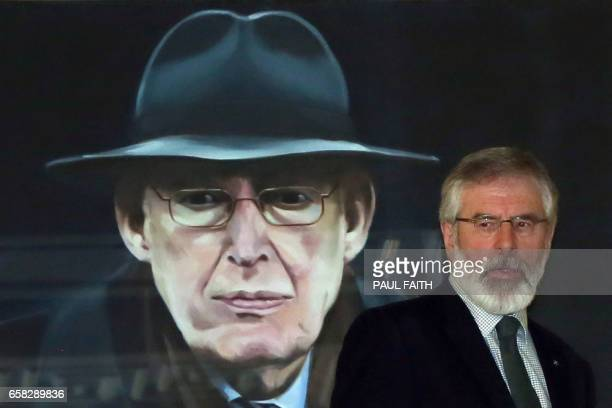 Sinn Fein President Gerry Adams walks past a portrait of Former First Minister Ian Paisley on his way to a press briefing at Stormont in Belfast on...
