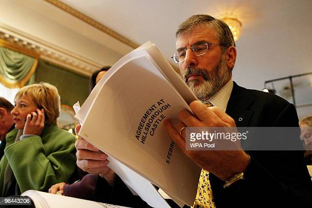 Sinn Fein's Gerry Adams looks at a copy of the Agreement during a press conference after a deal was announced concerning Northern Ireland's...