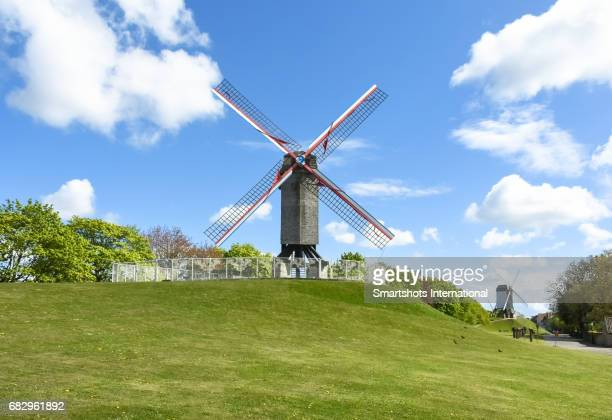 Sint Janhuysmolen windmill in Bruges with a second windmill on background under dramatic sky in Bruges, Flanders, Belgium