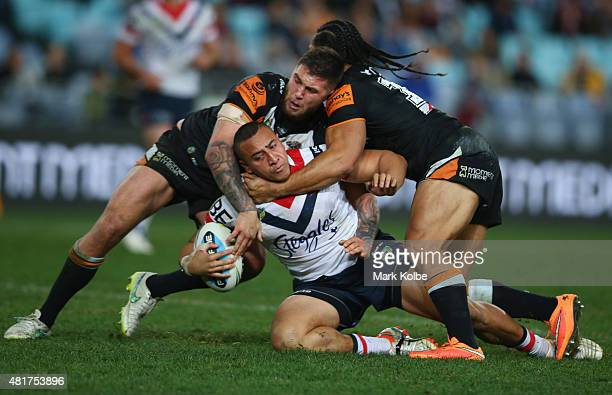 Sio Siua Taukeiaho of the Roosters is tackled during the round 20 NRL match between the Wests Tigers and the Sydney Roosters at ANZ Stadium on July...
