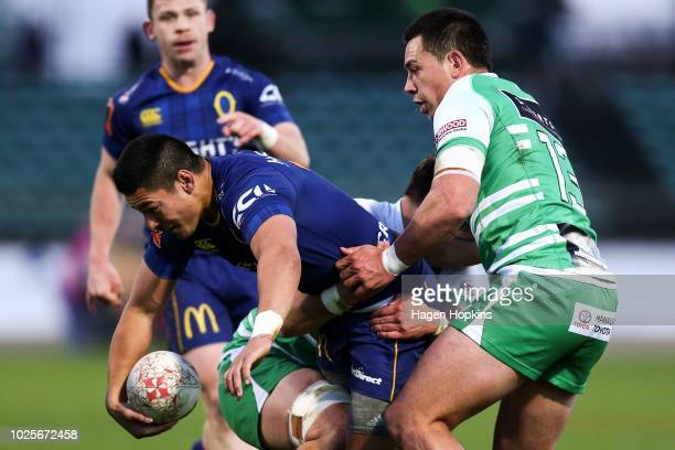 Sio Tomkinson of Otago is tackled by Liam Mitchell and Rob Thompson of Manawatu during the round three Mitre 10 Cup match between Manawatu and Otago...