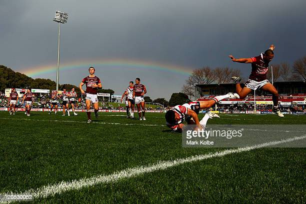 Sione Ala of the Sea Eagles jumps over Chris Taripo of the Roosters as he scores a try during the round 22 Toyota Cup match between the Manly...