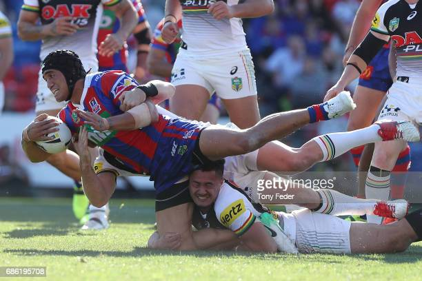 Sione Mata'Utia of the Knights is tackled by the Panthers defence during the round 11 NRL match between the Newcastle Knights and the Penrith...