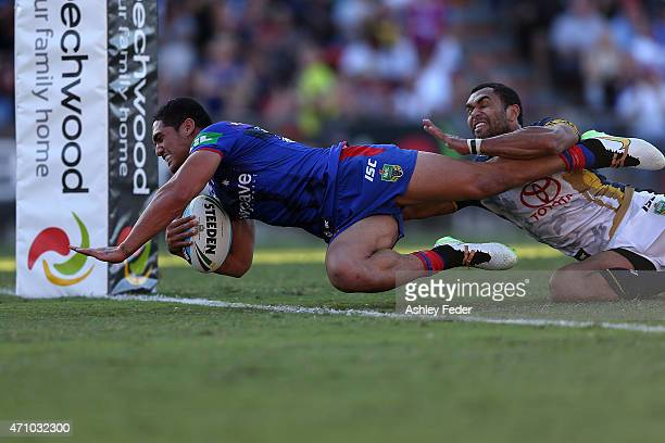 Sione Mata'Utia of the Knights scores a try ahead of Justin O'Neill of the Cowboys during the round eight NRL match between the Newcastle Knights and...