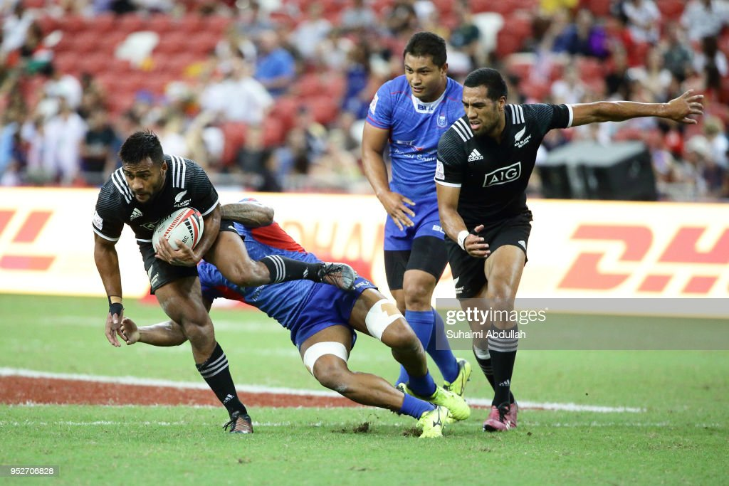 Sione Molia of New Zealand is tackled by Laaloi Leilua of Samoa during the 2018 Singapore Sevens 5th Place Play-Off match between New Zealand and Samoa at National Stadium on April 29, 2018 in Singapore.
