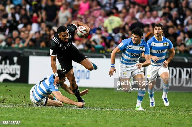 Sione Molia of New Zealand tries to break the tackle of Nicolas Menedez of Argentina during the Plate Final on the third and final day of the Hong...