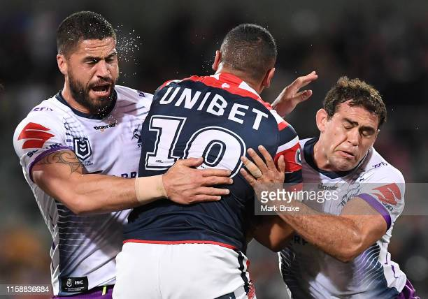 Siosiua Taukeiaho of the Roosters tackled by Jesse Bromwich of the Storm and Felise Kaufusi of the Storm during the round 15 NRL match between the...