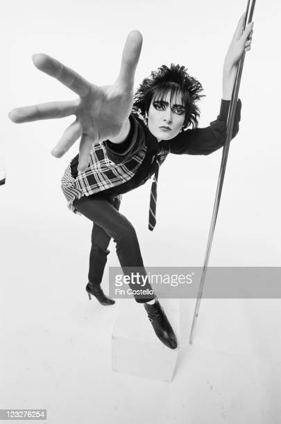 Siouxsie Sioux singer with British punk band Siouxsie and the Banshees poses holding onto a vertical stainless steel pole with her left hand with her...