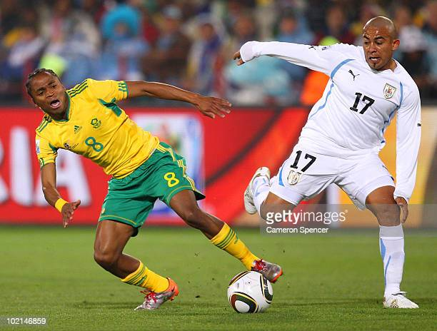 Siphiwe Tshabalala of South Africa tackles Egidio Arevalo of Uruguay during the 2010 FIFA World Cup South Africa Group A match between South Africa...