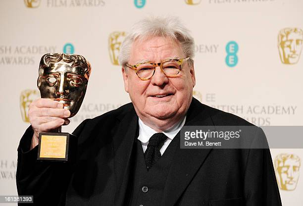 Sir Alan Parker winner of the BAFTA Fellowship poses in the Press Room at the EE British Academy Film Awards at The Royal Opera House on February 10...