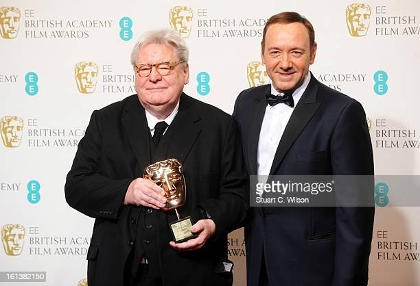 Sir Alan Parker winner of the Fellowship award poses in the press room with presenter Kevin Spacey at the EE British Academy Film Awards at The Royal...