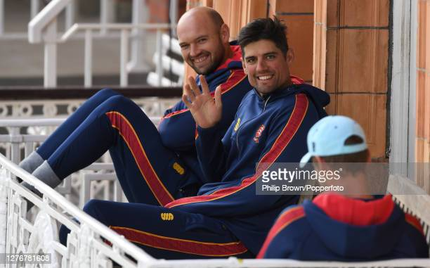 Sir Alastair Cook waves as he sits with Nick Browne of Essex on the dressing room balcony during the Bob Willis Trophy Final between Somerset and...