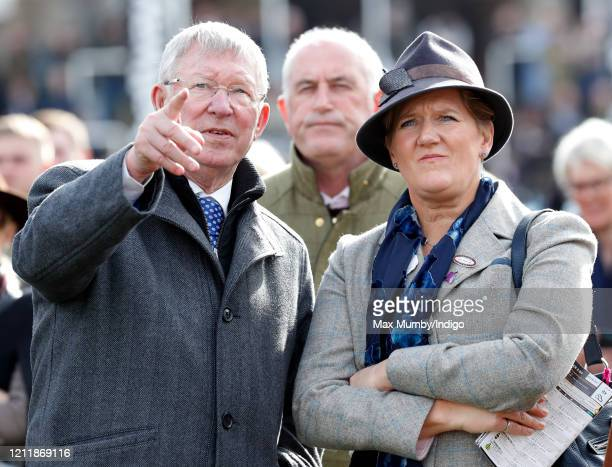 Sir Alex Ferguson and Clare Balding watch his horse 'Protektorat' run in the Coral Cup Handicap Hurdle race on day 2 'Ladies Day' of the Cheltenham...
