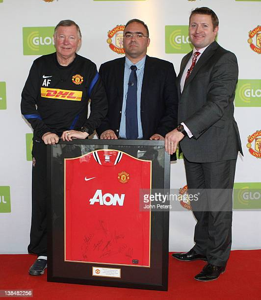 Sir Alex Ferguson and Commercial Director Richard Arnold of Manchester United present a signed shirt to Haris Kotsibos CEO of Globul after a press...