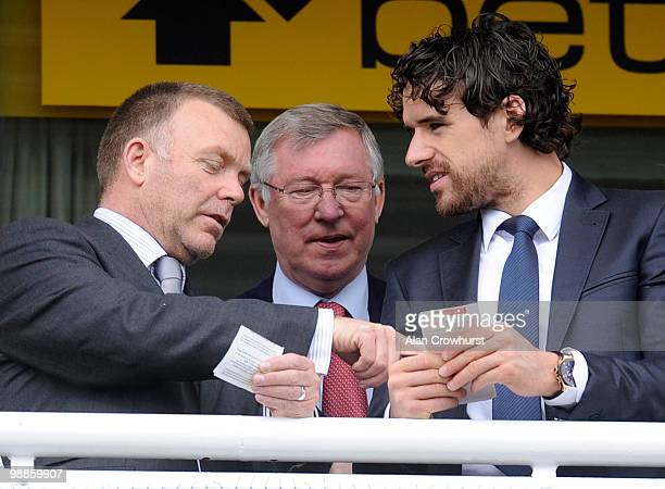 Sir Alex Ferguson checks the betting slips of Owen Hargreaves and a Manchester United coach at Chester racecourse on May 05 2010 in Chester England
