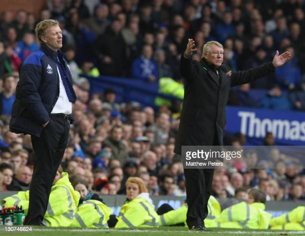 Sir Alex Ferguson of Manchester United and David Moyes of Everton watch from the touchline during the Barclays Premier League match between Everton...
