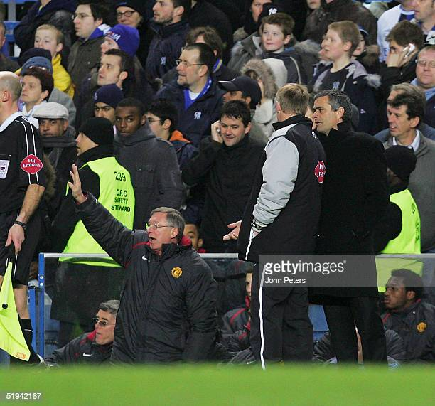 Sir Alex Ferguson of Manchester United and Jose Mourinho of Chelsea watch from the dugouts during the Carling Cup semifinal first leg match between...