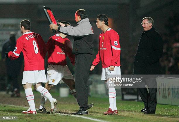 Sir Alex Ferguson of Manchester United brings on Wayne Rooney and Cristiano Ronaldo during the FA Cup Third Round match between Burton Albion and...