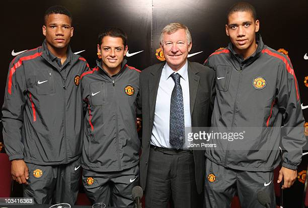 Sir Alex Ferguson of Manchester United poses with Bebe Javier 'Chicharito' Hernandez and Chris Smalling after a press conference to announce...
