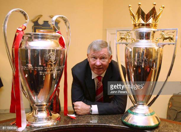 Sir Alex Ferguson of Manchester United poses with the UEFA Champions League trophy and the FA Barclays Premier League trophy after winning the UEFA...