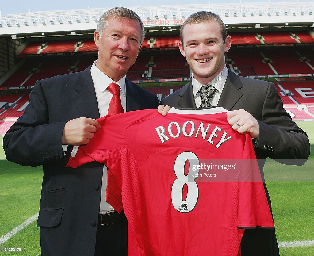 Sir Alex Ferguson of Manchester United poses with Wayne Rooney and a United shirt after a press conference to unveil Manchester United's new signing Wayne Rooney at Old Trafford on September 1 2004 in Manchester, England.