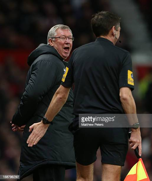 Sir Alex Ferguson of Manchester United shares a joke with assistant referee Andy Garratt during the Barclays Premier League match between Manchester...