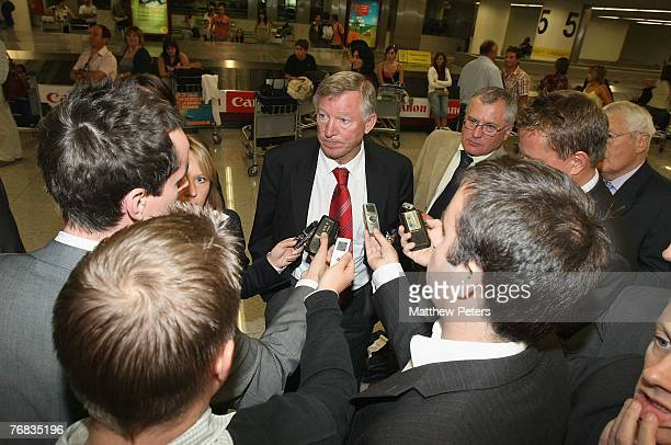 Sir Alex Ferguson of Manchester United speaks to journalists after arriving at Lisbon Airport ahead of their UEFA Champions League match against...