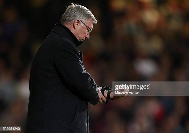 Sir Alex Ferguson the head coach / manager of Manchester United checks his watch