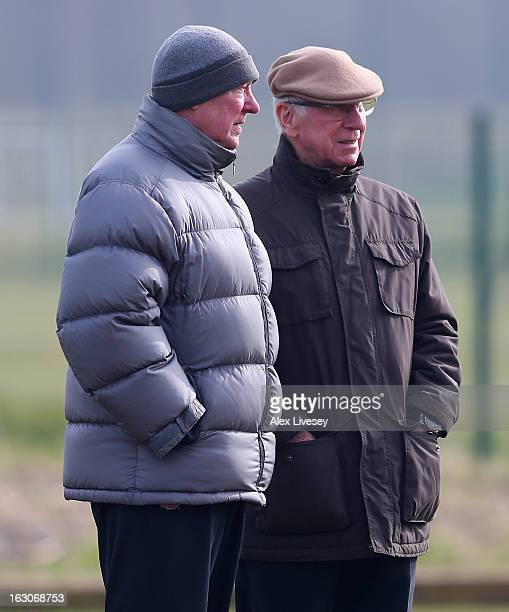 Sir Alex Ferguson the manager of Manchester United talks with Sir Bobby Charlton during a training session at Carrington Training Ground on March 4...