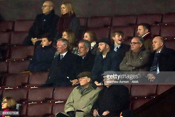 Sir Alex Ferguson watches with golfer Sam Torrance and Mike Phelan during the FA Cup fourth round match between Manchester United and Wigan Athletic...