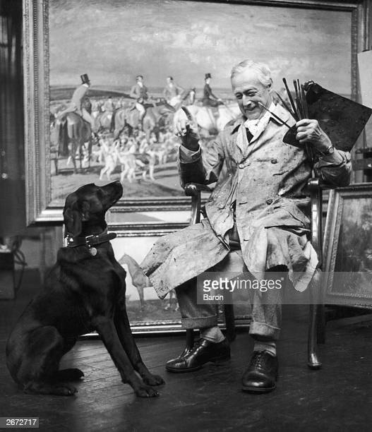 Sir Alfred James Munnings the English painter and President of the Royal Academy playing with his dog in front of one of his works in his studio