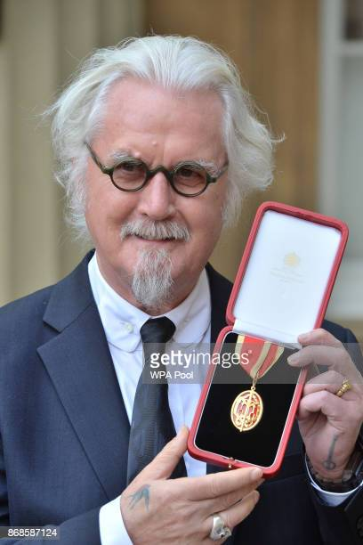 Sir Billy Connolly poses after being knighted by the Duke of Cambridge during an Investiture ceremony at Buckingham Palace on October 31 2017 in...