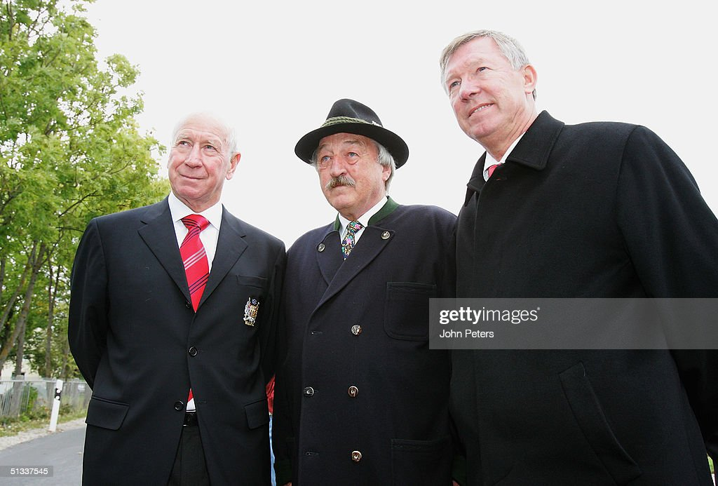 Sir Bobby Charlton (L) and Sir Alex Ferguson (R) of Manchester United pose with Georg Fischer, a fireman who attended the Munich Air Crash on his first day of work, at the ceremony to unveil the new memorial to those killed in the Munich Air Disaster on September 22, 2004 in Munich, Germany. 23 people were killed on February 6, 1958, when a plane carrying members of the Manchester United squad returning from a European Cup match in Belgrade crashed in the small village of Kirchtrudering.