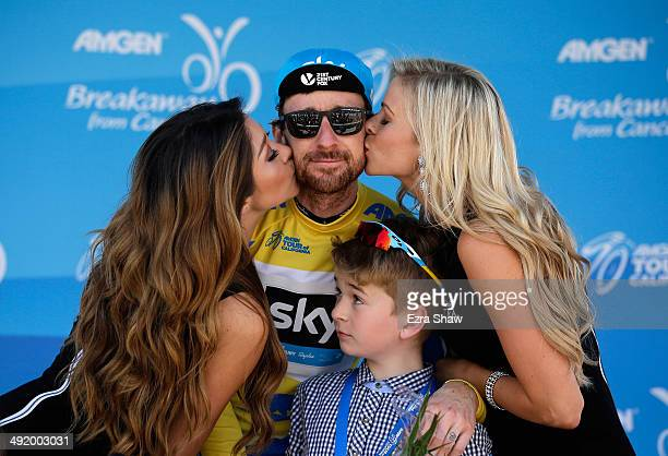 Sir Bradley Wiggins of Great Britain riding for Team Sky is kissed by the flower girls while his son, Ben, looks on following stage eight of the 2014...