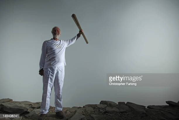 Sir Chris Bonington holds the Olympic torch on the summit of Mount Snowdon on May 29 2012 in Llanberis United Kingdom Legendary mountaineer Sir Chris...
