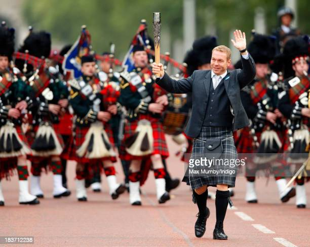 Sir Chris Hoy carries the 2014 Glasgow Commonwealth Games Baton down The Mall during the launch of the Queen's Baton Relay at Buckingham Palace on...