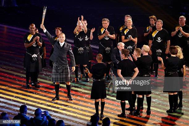 Sir Chris Hoy holds up the baton during the Opening Ceremony for the Glasgow 2014 Commonwealth Games at Celtic Park on July 23, 2014 in Glasgow,...