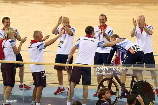 Sir Chris Hoy of Great Britain celebrates winning the Gold medal in the Men's Keirin Track Cycling Final with coaching staff on Day 11 of the London...