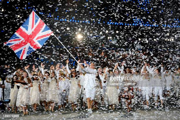 Sir Chris Hoy of the Great Britain Olympic cycling team carries his country's flag as he leads Great Britain into the stadium during the Opening...