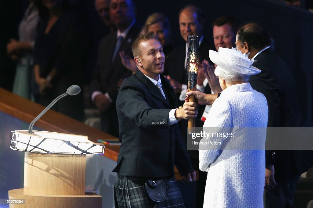 Sir Chris Hoy presents Prince Imran the CGF President the baton as Queen Elizabeth II, Patron of the CGF looks on during the Opening Ceremony for the Glasgow 2014 Commonwealth Games at Celtic Park on July 23, 2014 in Glasgow, Scotland.